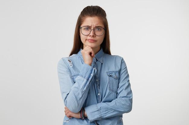Portret van een meisje met een bril en een arm op de taille en een ander op de kin op wit