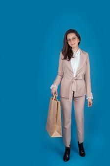 Portret van een meisje met een bril en een licht pak een meisje met een papieren zak uit de winkel isoleer op een blauwe achtergrond