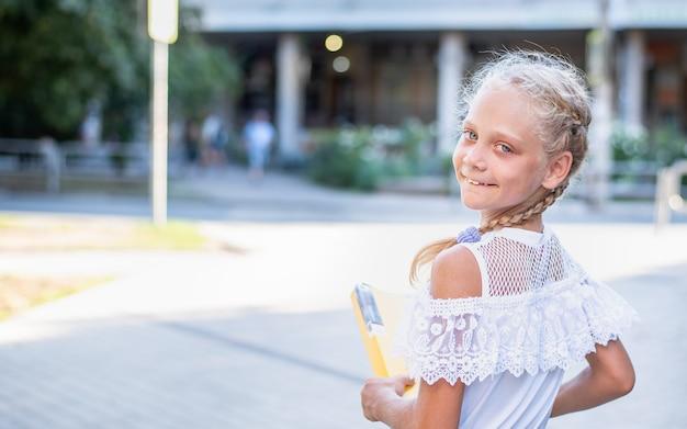 Portret van een meisje met een map die naar school gaat