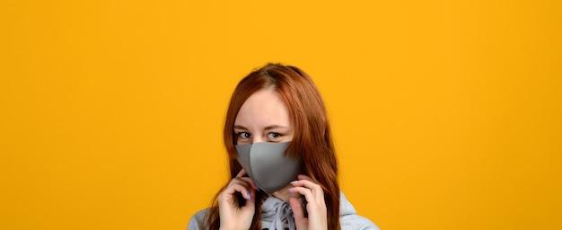 Portret van een meisje met een masker, dat een rubberen handschoen aantrekt. gele achtergrond. isolatie, covid-19.
