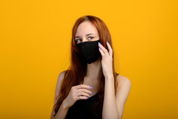 Portret van een meisje met een masker, dat een rubberen handschoen aantrekt. gele achtergrond.
