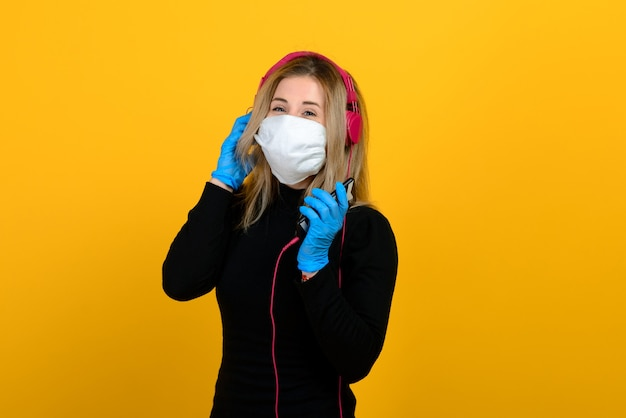 Portret van een meisje met een medisch masker, dat een rubberen handschoen aantrekt. gele en grijze achtergrond. ruimte kopiëren.