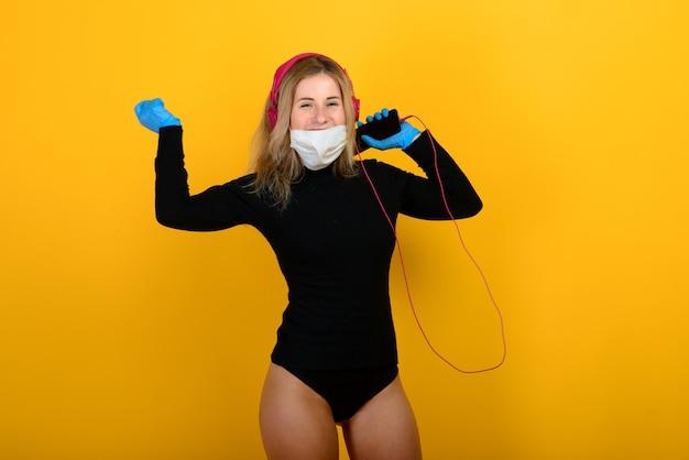 Portret van een meisje met een medisch masker, dat rubberen handschoen aantrekt. gele en grijze achtergrond.