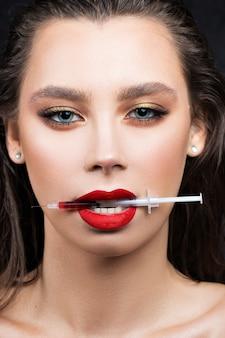Portret van een meisje met een spuit voor lipinjecties gevuld met bloed