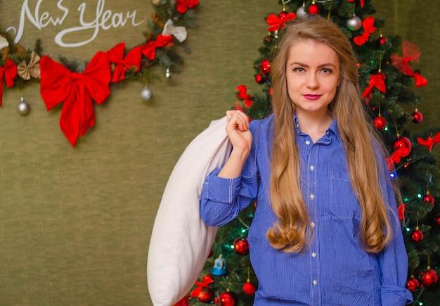 Portret van een meisje met felrode lippen, lang blond haar jong meisje in een blauw shirt met een wit kussen in zijn handen
