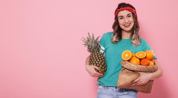 Portret van een meisje met fruit op een roze muur