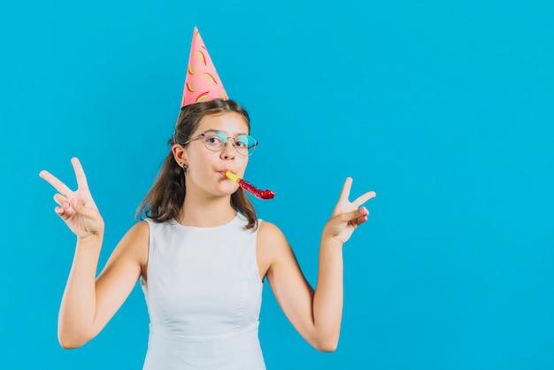 Portret van een meisje met gesturing vredesteken van de partijhoorn op blauwe achtergrond