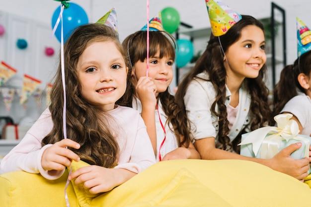 Portret van een meisje met haar vrienden die van de verjaardagspartij genieten