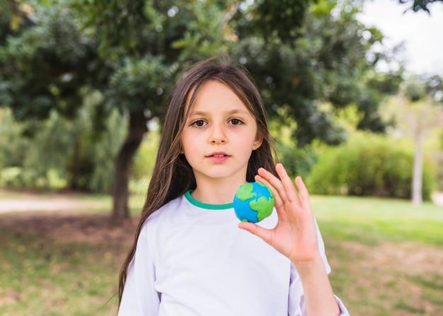 Portret van een meisje met klei wereld bol in de hand