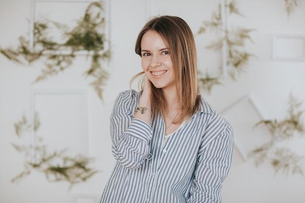 Portret van een meisje met krullen in een gestreept overhemd op een witte muur met planten