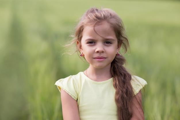 Portret van een meisje met lang haar in een veld