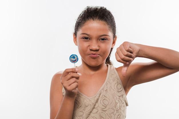 Portret van een meisje met lolly gebaren duimen naar beneden