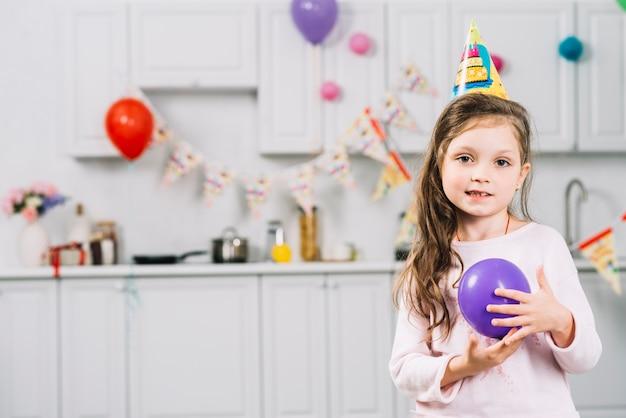 Portret van een meisje met purpere ballon die zich in keuken bevinden