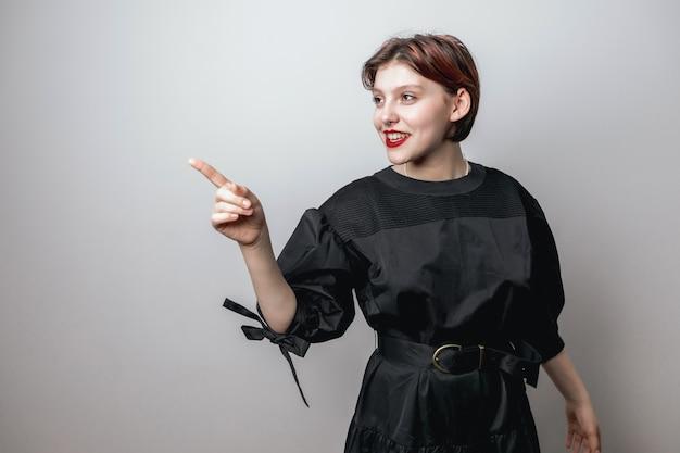 Portret van een meisje met rode lippen in een modieuze zwarte jurk op een lichte achtergrond