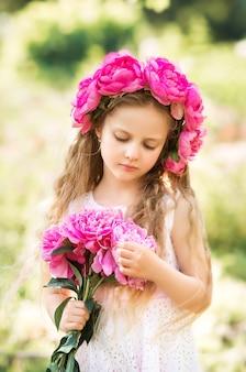 Portret van een meisje met roze bloemen. een krans van pioenrozen op het hoofd van het kind..