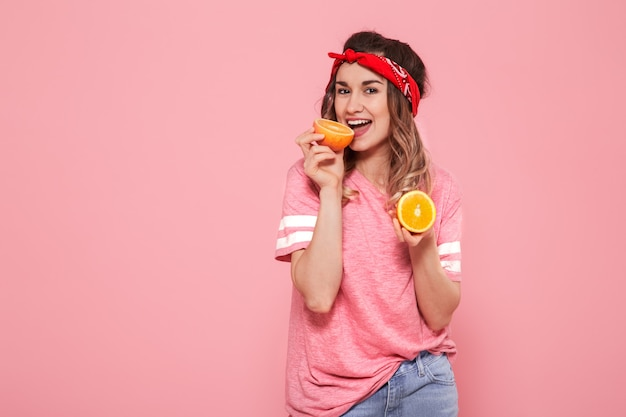 Portret van een meisje met sinaasappelen in hand, op een roze achtergrond