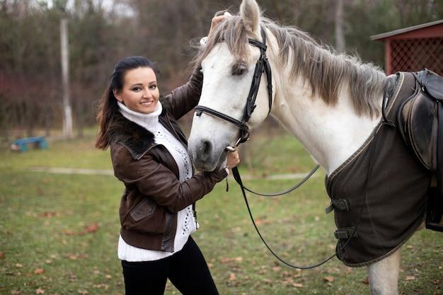Portret van een meisje naast een wit paard