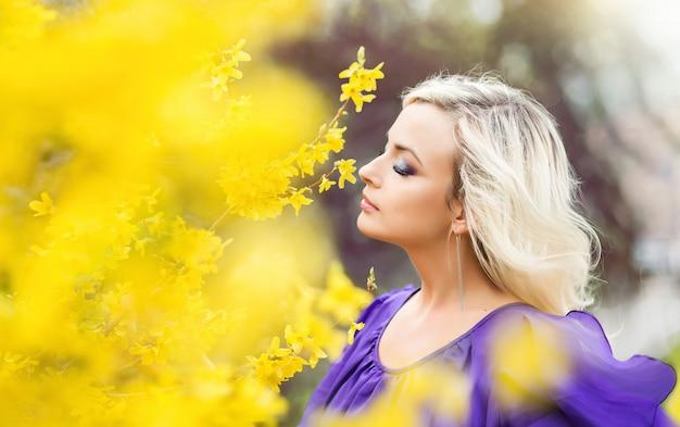 Portret van een meisje op een achtergrond van gele bloemen. mooie vrouw in een paarse jurk met bloeiende forsythia. concept van parfumerie en cosmetica