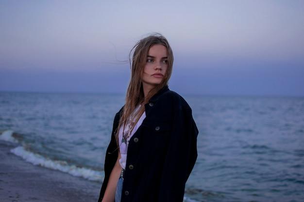 Portret van een meisje op het strand. zonsondergang. haar wapperen in de wind