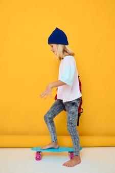 Portret van een meisje rijdt op een skateboard met een rode rugzak geïsoleerde achtergrond