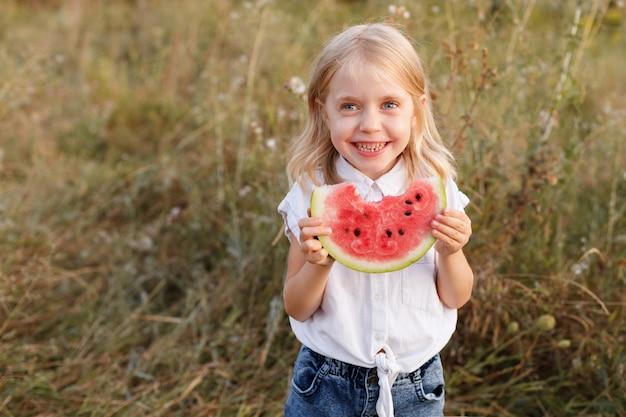 Portret van een meisje van 5 jaar oud met een watermeloen in de zomer tijdens een wandeling