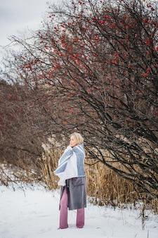 Portret van een meisje van europese uitstraling op een winterwandeling, gras, bos, veld, hoed, gezondheid. meisje met een plaid, in een plaid wikkelen, sjaal