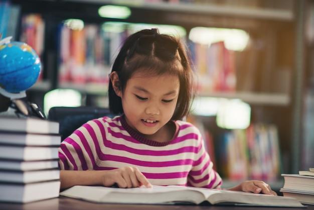Portret van een meisje van het studentenkind die bij bibliotheek bestuderen