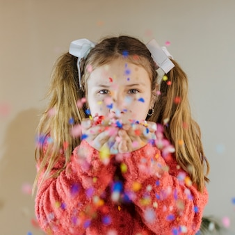 Portret van een meisjes blazende confettien