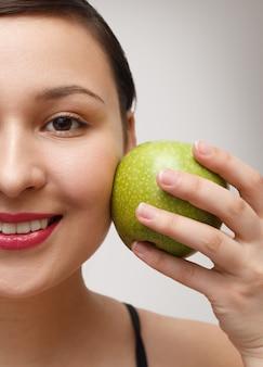 Portret van een meisjes half gezicht met een appel die tegen haar wang leunt. op een grijze achtergrond