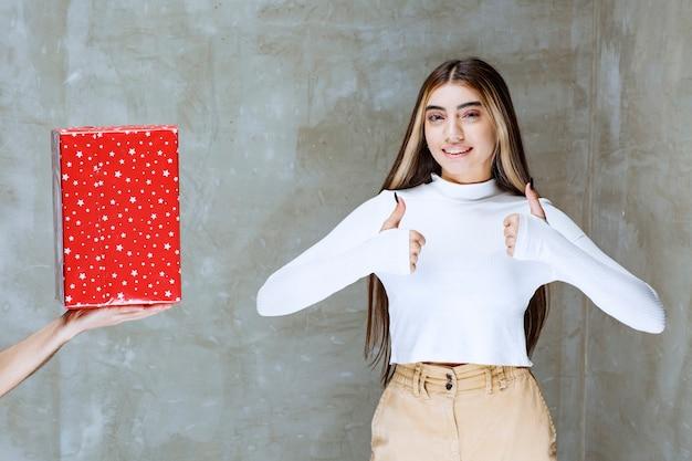 Portret van een meisjesmodel dat duimen toont die dichtbij huidige doos over steen wordt geïsoleerd