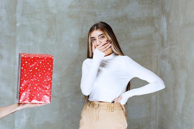 Portret van een meisjesmodel dat zich dichtbij huidige doos bevindt die over steen wordt geïsoleerd