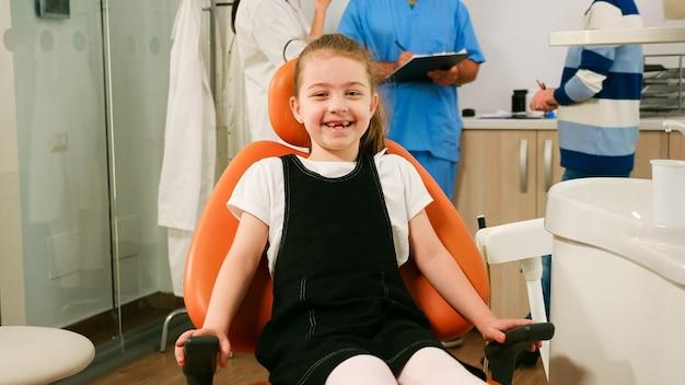 Portret van een meisjespatiënt die naar de camera kijkt en lacht, wachtend op een pediatrische stomatoloog in de tandheelkundige afdeling. kind liggend op stomatologische stoel glimlachend naar webcam terwijl verpleegster en dokter praten met moeder