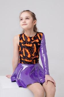 Portret van een meisjesturner in een heldere gymnastische maillot
