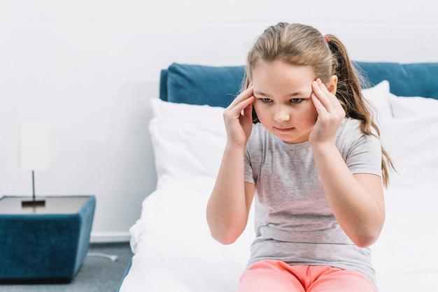 Portret van een meisjeszitting op bed die hoofdpijn hebben