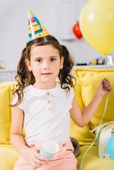 Portret van een meisjeszitting op in hand de ballon van de bankholding