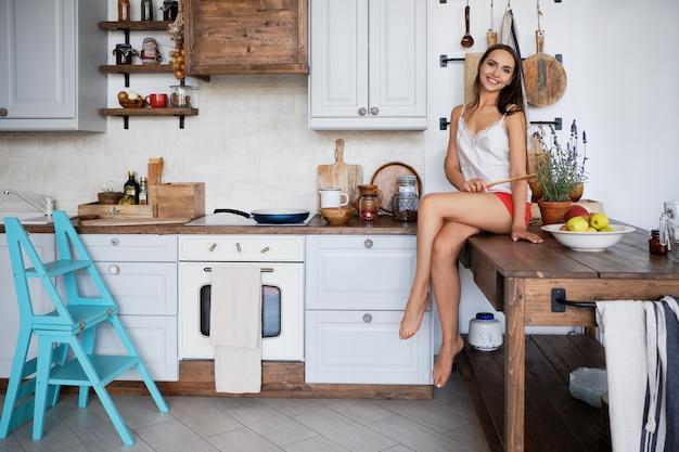 Portret van een meisjeszitting op keukenlijst door het fornuis, kokende saus in pan