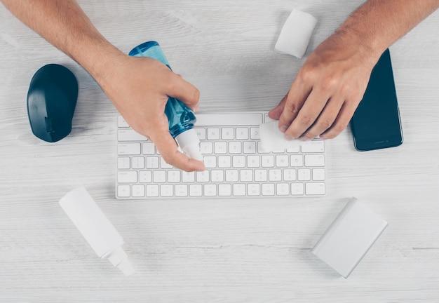 Portret van een mens bij lichte houten achtergrond met desinfecterend middel dat zijn toetsenbord en dingen reinigt