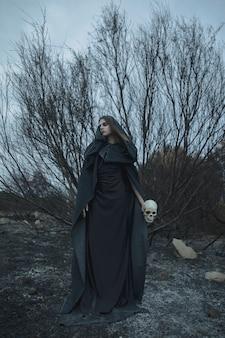 Portret van een mens die een schedel met de herfsttakken houden op achtergrond