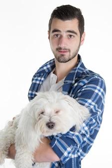 Portret van een mens die een witte hond maltese bischon geïsoleerd houdt