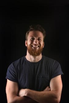 Portret van een mens die en met gekruiste en zwarte wapens glimlacht
