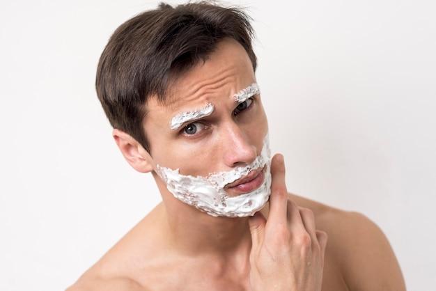 Portret van een mens die met het scheren van schuim op gezicht denkt