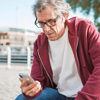 Portret van een mens die oogglazen draagt die smartphone bekijken