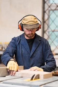 Portret van een mens die veiligheidsbril en oorverdedigers draagt die houten blok op lijstzaag snijden