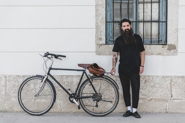 Portret van een mens die zich met fiets bevindt die op muur leunt