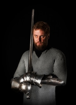 Portret van een middeleeuwse ridder met een baard in maliënkolder met een ridderzwaard in zijn hand en pantser, geïsoleerd op een donkere muur