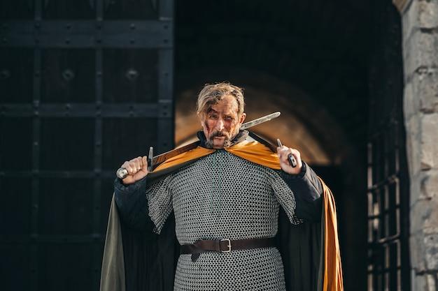 Portret van een middeleeuwse senior krijger in harnas na een gevecht met bloed op zijn gezicht. de krijger heeft twee zwaarden in zijn handen