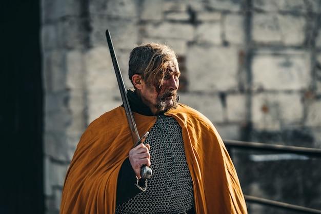 Portret van een middeleeuwse senior krijger in harnas na een gevecht met bloed op zijn gezicht. de krijger houdt het zwaard in zijn handen