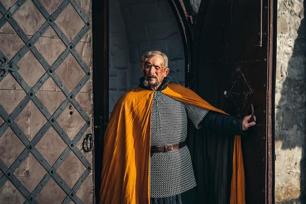 Portret van een middeleeuwse senior krijger man in harnas na een gevecht met vies en met bloed besmeurd gezicht