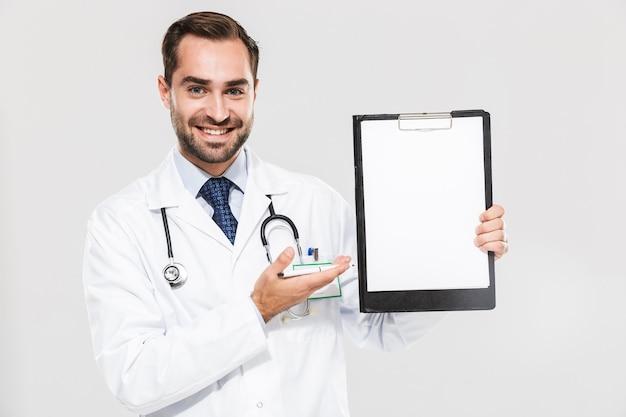 Portret van een minzame jonge arts die lacht en een gezondheidskaart vasthoudt die over een witte muur wordt geïsoleerd