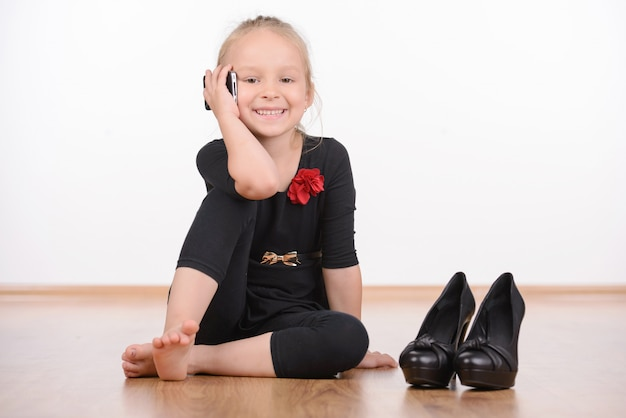 Portret van een mode-meisje in een zwarte jurk en grote schoenen.